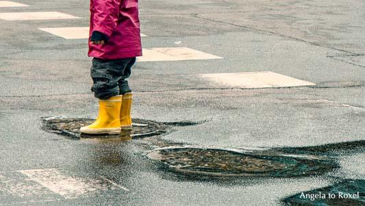 Kind in rotem Regenmantel und gelben Gummistiefeln steht in einer Pfütze