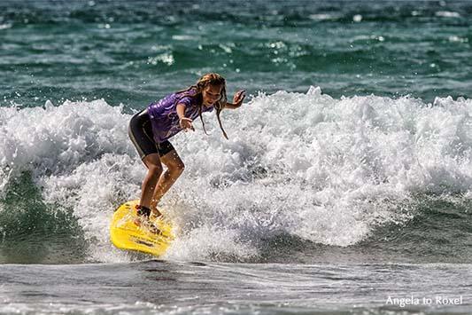 Surferin auf einem gelben Surfbrett beim Wellenreiten am Atlantik, hält die Balance auf einer Welle, am Strand von Biarritz, Côte des Basque 2012