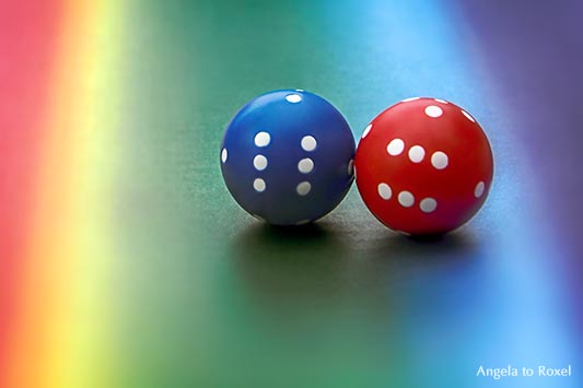 Fotografien kaufen: Alles rund - Sechserpasch gwürfelt: zwei runde Würfel, rot und blau auf regenbogenfarbenem Untergrund | Ihr Kontakt: A. to Roxel