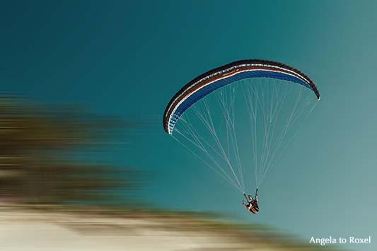 Fotografie: Im Sommerwind, Paraglider fliegt über der Dune du Pilat, setzt zur Landung an, unscharfer Hintergrund | Ihr Kontakt: Angela to Roxel