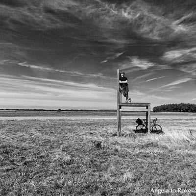 Stuhl, Unterstand nahe Born, Mann steht auf einem großformatigen Stuhl, schwarzweiß, surreale Wirkung, Halbinsel Fischland/Darß | Angela to Roxel