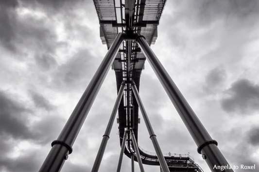 Beine einer Achterbahn von unten, Schwarzweißaufnahme, dramatischer Wolkenhimmel