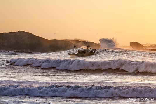 Fotografien kaufen: Coming home, Fischerboot in der Brandung bei Sonnenuntergang, Einfahrt in den Hafen, Essaouira, Marokko | Kontakt: Angela to Roxel