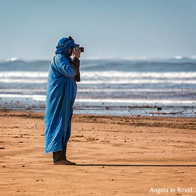 Fotograf in blauer Kleidung fotografiert am Strand, Plage Tagharte, Essaouira