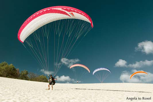 Ein Paraglider auf der Dune du Pilat beim Küstenstart, drei weitere Gleitschirme im HIntergrund