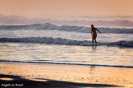 Silhouette einer Surferin in den auslaufenden Wellen der Brandung am Abend, Essaouira