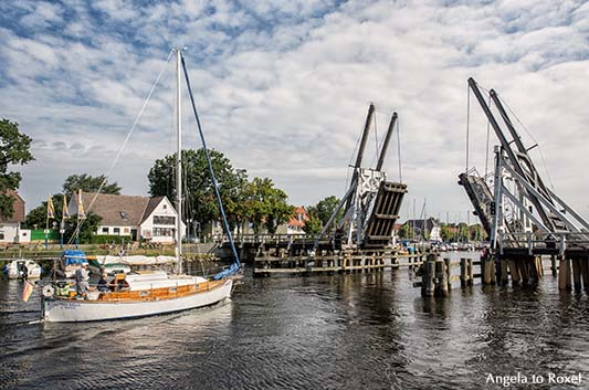 Geöffnete Holzklappbrücke über den Ryck, davor ein Segelboot, bereit zur Durchfahrt - Greifswald
