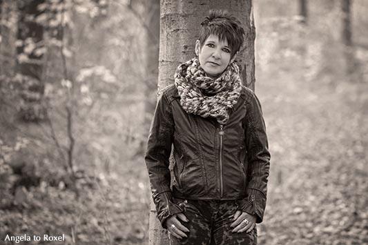 Frau an einem Baum im Herbstwald, monochrom