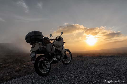 Parkendes Motorrad am Nordkap, dahinter die tiefstehende Mitternachtssonne, Nordkap, Insel Magerøya