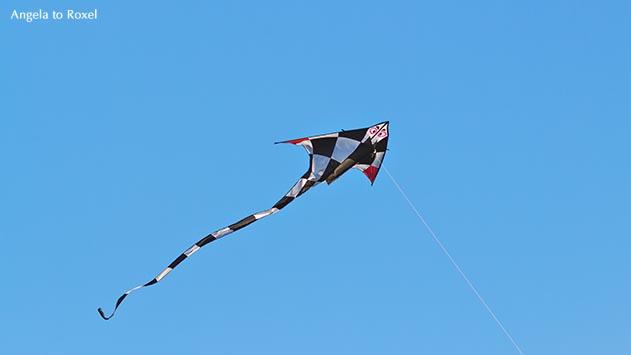 Fotografie: Fly a Kite - Ein schwarzweiß karierter Drachen fliegt vor blauem Himmel, Fesseldrachen oder Kite, Île d'Oléron, Frankreich - Stockfoto