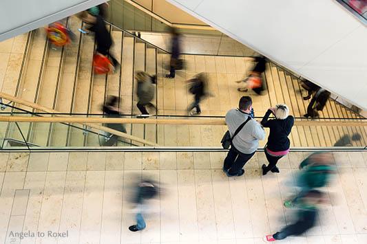 Moment - Menschen in Eile, Menschenmenge unterwegs in einem Einkaufszentrum, Langzeitbelichtung mit Bewegungsunschärfe
