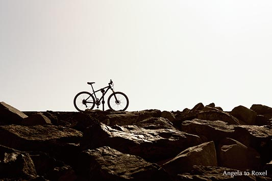 Fahrrad steht auf Felsblöcken, Gegenlicht,  Las Teresitas
