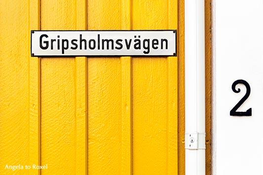 Straßenschild Gripsholmsvägen, an einem gelbweiß gestrichenen Schwedenhaus