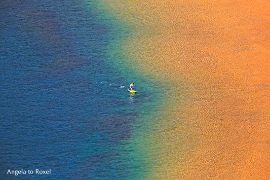 Fotografie: Over the Rainbow, einzelne Person mit Stehpaddel an der Küste, Stand Up Paddling, Regenbogenfarben in Las Teresitas