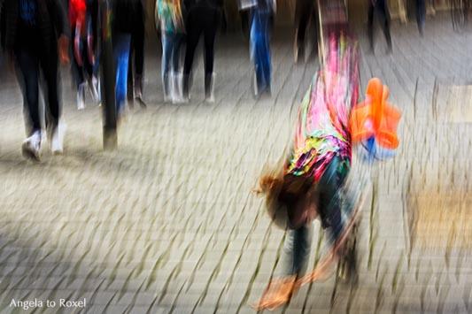 Kunstfotografie kaufen: Clown schlägt ein Rad, im Hintergrund Passanten, Bewegungsunschärfe, Wischtechnik, Bielefeld | Ihr Kontakt: Angela to Roxel