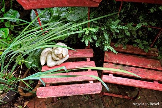 Skulptur auf einem roten Gartenstuhl, Stillleben in Rilkes verwunschenem Garten