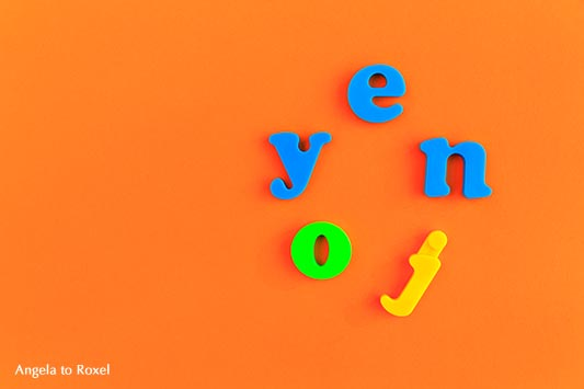 das Wort enjoy, bunte Buchstaben liegen im Kreis, Hintergrund orange | Ihr Kontakt: Angela to Roxel