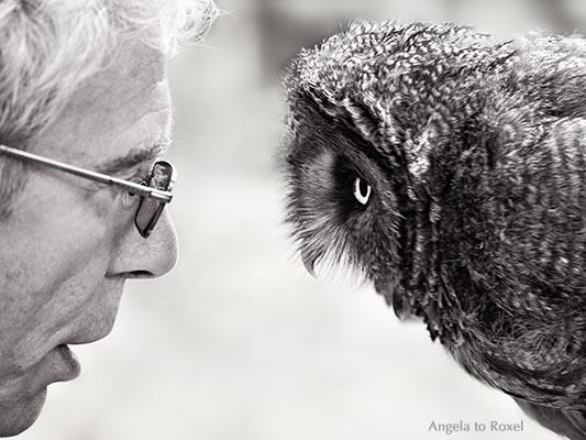 Der Falkner Ludger Kluthausen und einer seiner Bartkäuze (Strix nebulosa) im Gespräch, close-up, monochrom, Falknerei Kasselburg, Vulkaneifel 2015