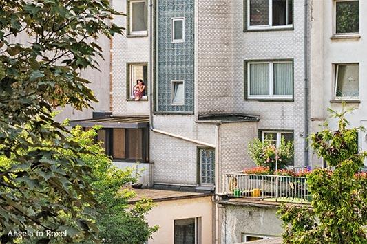 Fotografie: Looking for paradise, junge Frau sitzt in einem Fenster und schaut gedankenverloren, Hinterhof in einer Stadt | Kontakt: Angela to Roxel