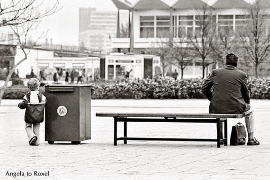 Mann sitzt auf einer Bank im Stadtzentrum, Aktentasche zwischen den Beinen, ein Junge links von ihm, Rückansicht, schwarzweiß, analog - Ostberlin 1981