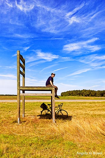 Man sitting on a chair with his bike below, oversized chair, animal shed on a field near Born, side view - Fischland/Darß