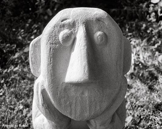 Fotografie: Der Denker, Kopf in aufgestützter Hand, Skulptur im Garten, Nahaufnahme mit Seitenlicht, Licht und Schatten, monochrom - Bildlizenz