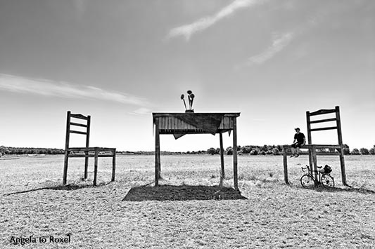 Man sitting on a chair with his bike below, oversized table and chair, animal shed on a field near Born, black and white - Fischland/Darß