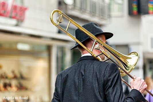 Fotografie Bilder kaufen: Trombone man walking, Mann geht mit einer Posaune auf der Schulter durch die Stadt, City, Bielefeld | Angela to Roxel