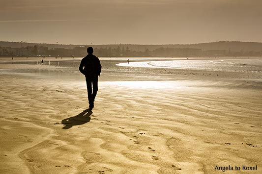 Man walking on Plage Tagharte in winter, backlight, early morning light - Essaouira, Morocco