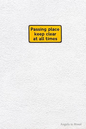 Fotografie Freiraum schaffen: Gelbes Schild an leerer Wand: Passing place keep clear at all times, Platz freihalten, Stromnes, Orkney 2015 - Stockfoto
