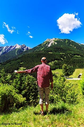 Mann hält eine Kaffeetasse in der Hand und schaut auf die Berge im Hintergrund, Rückenansicht - Graubünden