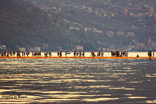 "Photography: The Floating Piers - Lake Iseo, People on the walkway, Christo's ""The Floating Piers"" in the evening light, backlight, Italy 2016"