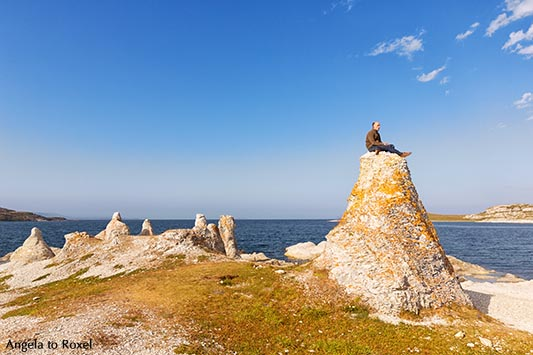 Hiker sitting on one of the legendary dolomite rocks on Porsangerfjorden, near Lakselv, Porsanger, Porsáŋgu, Porsanki, Finnmark County, Norway