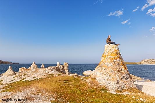 Hiker sitting on one of the legendary dolomite rocks on Porsangerfjorden, near Lakselv, Porsanger, Porsáŋgu, Porsanki, Finnmark County, Norway