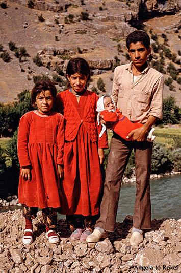 Fotografie: Vier Geschwister, zwei Mädchen und ein Junge mit einem Baby im Arm stehen am Straßenrand, Provinz Hakkari, Türkei 1986 | Angela to Roxel