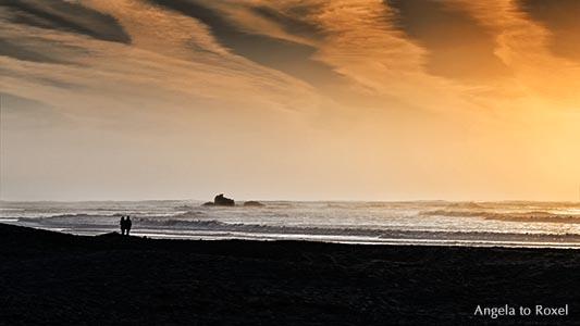 Paar steht bei Sonnenuntergang am Strand und betrachtet die Ruine eines Wachturms am Strand, Silhouetten, Essaouira, Marokko 2014