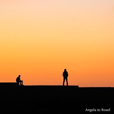 Fotografie: Mann auf einer Mauer, sitzt, steht, Silhouette, Sonnenuntergang im Hafen, Essaouira, Marokko | Ihr Kontakt: Angela to Roxel