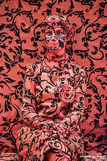 Straßenkünstlerin trägt Kleidung und Schminke in der Farbe und im Muster des Hintergrundes, rot, Valencia - Spanien 2016