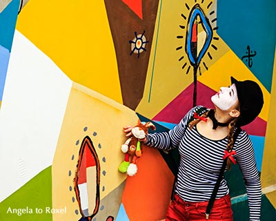 Fotografie: Weiblicher Clown betrachtet bunt bemalte Wand, Bielefeld spontan, April 2016 | Ihr Kontakt: Angela to Roxel