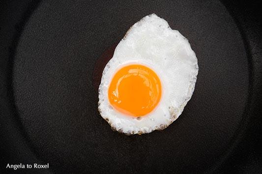 Food-Fotografie: sunny side up - gebratenes Wachtelei, Spiegelei in einer schwarzen Pfanne, von oben, März 2016 - Stockfotografie, Bildlizenz