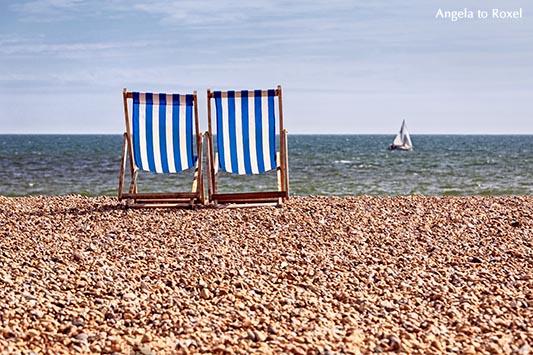 Fotografie: Zwei Deckchairs am Kiesstrand, im Hintergrund ein Segelboot, das über den Ärmelkanal fährt, Brighton, England 2014 - Stockfoto, Bildlizenz