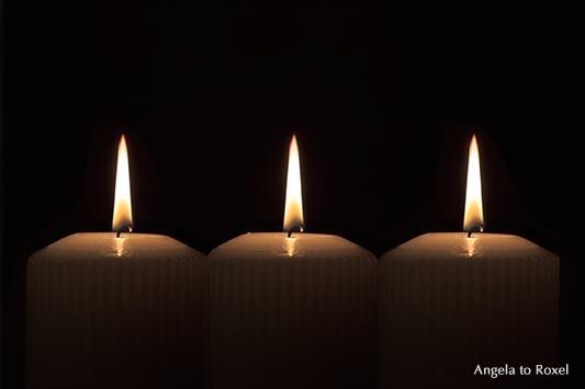 Fotografie: Drei Kerzen, leuchten in der Dunkelheit, Flammen im Dunklen, Zählimpuls oder das Symbol für Dreiheit, Licht in der Dunkelheit, Stockfoto
