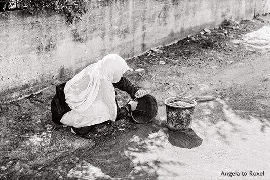 Drusische Frau in den Golanhöhen, säubert die Straße, analog, monochrom - Golanhöhen 1980