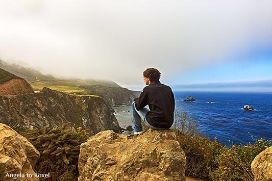 Junger Mann in Big Sur, sitzt auf einem Felsen an der Pazifikküste und schaut auf die Berge der Santa Lucia Range, Highway No 1 - Kalifornien 2011
