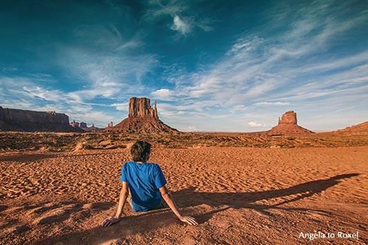 Junger Mann sitzt abends im Monument Valley und schaut zu den Butten, Rückenansicht, langer Schatten - Utah 2011