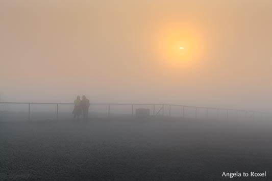 Paar auf der Nordkapp-Plattform beobachtet, wie die Mitternachtssonne durch den Nebel bricht - Norwegen 2014