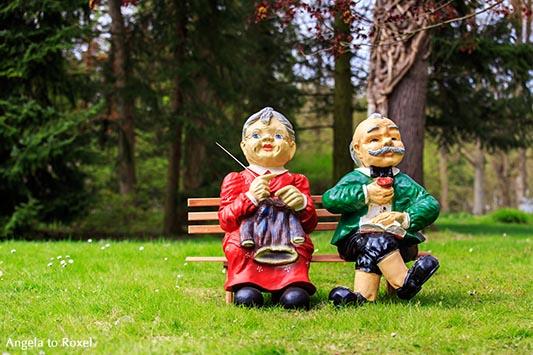 Fotografie: Comes a time - Zwei Gartenfiiguren, Oma und Opa sitzen nebeneinander auf einer Bank im Park, sie strickt, er liest - Bad Pyrmont 2013