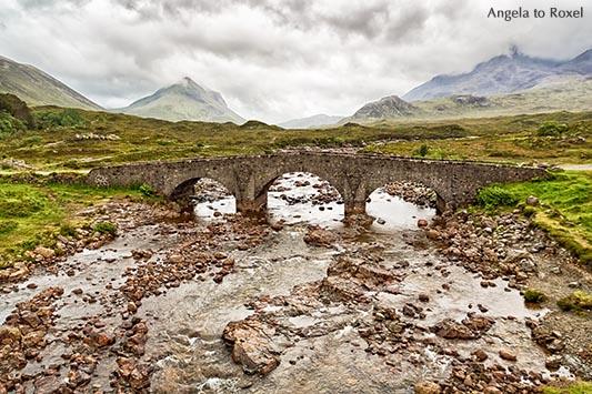 Die alte Steinbrücke Sligachan Bridge auf der Isle of Skye, im Hintergrund die Cullins unter Regenwolken, Schottland 2015 - Bildlizenz, Stockfoto