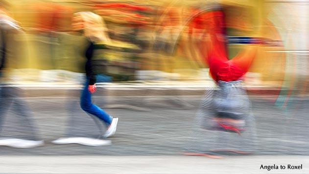 Zwei Passanten gehen in der Bielefelder Innenstadt an Schaufenstern vorbei, ein Clown schlägt hinter ihnen ein Rad, Bewegungsunschärfe - Bielefeld