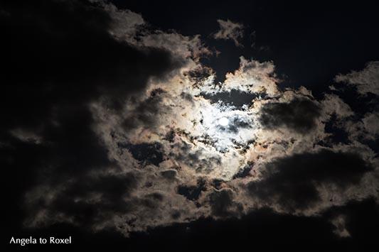 Fotografie: Sehr dunkler, stark bewölkter Himmel, Sonne hinter dunklen Wolken, dramatische Atmosphäre, Gegenlicht, Blick nach oben - Stockfoto